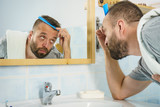 Man using comb in bathroom