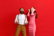 young happy couple won emotionally celebrating win on colored red background.