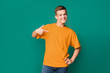 Teenager pointing at copy space on his t-shirt