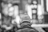Man with woolen yellow hat and silver headphones as seen from the back hearing music in the city - 238689244