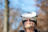 Mesmerized man wearing VR glasses exploring city park in winter - 238689602