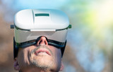 Mesmerized man wearing VR glasses exploring city park in winter - 238689804