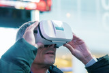 Excited young man wearing a pair of VR glasses exploring Times Square - 238690004