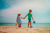 cute boy and girl walk on tropical beach vacation