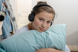 young teenage sitting on bed in bedroom listen to music with headphones