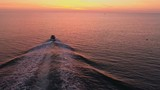 Aerial view. Flying over the boat and wakesurfer in sea during sunset - 238701821