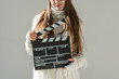 cropped image of woman in fashionable winter sweater and scarf holding clapper board isolated on grey