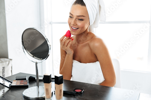 Leinwanddruck Bild Beautiful young woman wrapped in a towel