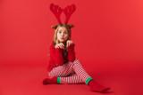 Cheerful little girl wearing Christmas raindeer costume - 238714895