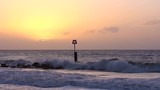 Sun Rising Behind Clouds on Wavy Beach with Groyne in Bournemouth South Coast England - 238715615