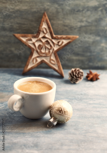 Cup of coffee, Christmas bauble and a wooden Christmas star. Christmas time. Rustic wooden background. Copy space.