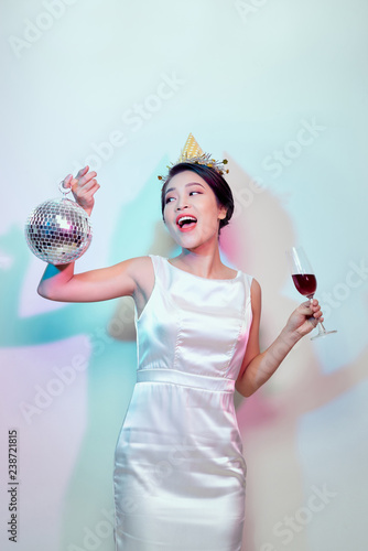 Portrait of a happy beautiful woman in white dress having a party and drinking champagne while standing with disco ball isolated over light background - 238721815