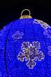 Leinwandbild Motiv Christmas street lights, blue and yellow leds. Big bauble.