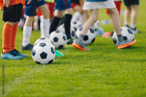 Football practice for youth. Children soccer training background. Group of young boys training soccer drills on green grass.