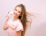 Cute smiling little girl child drying her long hair with hair dryer