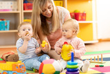 babysitter and children playing together in nursery or at home
