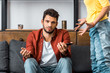 frustrated man sitting on sofa and showing shrug gesture near angry girlfriend