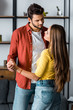 selective focus of happy bearded man dancing with girlfriend in living room