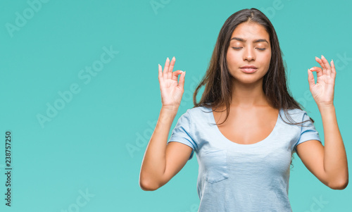 Leinwanddruck Bild Young beautiful arab woman over isolated background relax and smiling with eyes closed doing meditation gesture with fingers. Yoga concept.
