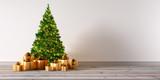 Grüner Weihnachtsbaum vor heller Wand mit goldenen Geschenken