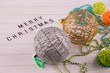 Big holiday balls laying on white wooden table near words Merry Christmas