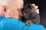 grey cat sitting on a man's shoulder