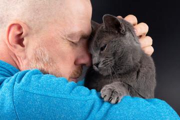 grey cat sitting on a man's shoulder © photosaint