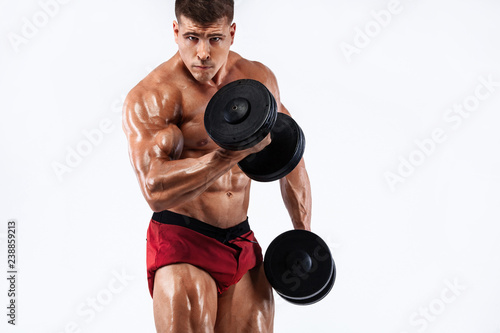 Brutal strong muscular bodybuilder athletic man pumping up muscles with dumbbell on white background. Workout bodybuilding concept. Copy space for sport nutrition ads. - 238859213
