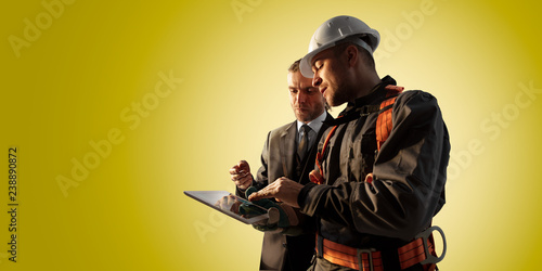 Foto Murales Windmill engineer and businessman planing new ecology project. they standing and looking in tablet. Color studio background