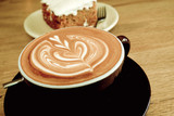 Hot Latte Coffee with Carrot Cheesecake on Wooden Table