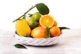 white ceramic basket with fresh citrus fruit. White background