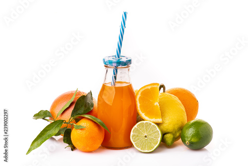 composition of fresh citrus with bottled juice and drinking straw. White background