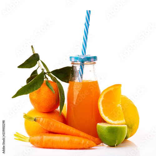 composition of fresh citrus and carrots with bottled juice and drinking straw. White background