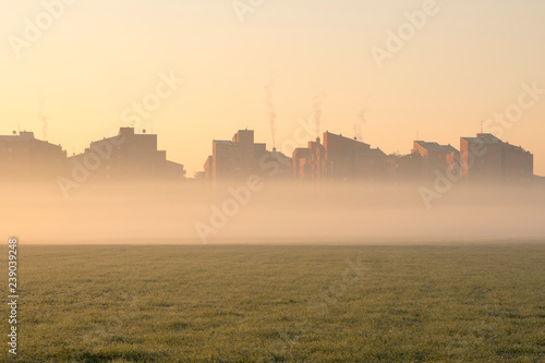 Cityscape at sunrise. Houses on the outskirts of the city with fog at dawn in winter. Smoke comes out of the chimneys. - 239039248