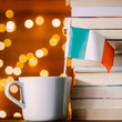 White cup with italy flag near books on fairy lights background