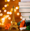 Christmas Santa Claus hat with Eiffel tower and pile of books with fairy lights on background