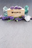 Wellness - word burnt in wood with purple lavender flowers, amethyst, fluorite and quartz crystals on slate background - 239095068