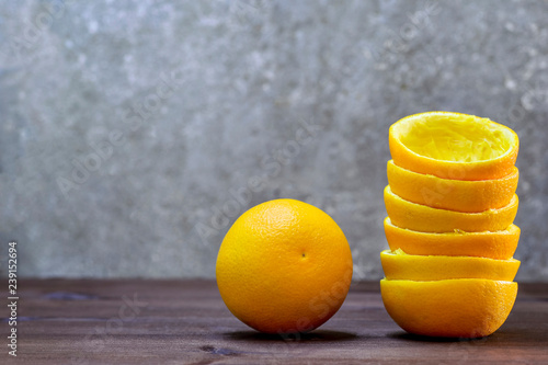 A composition of halves of orange peel and one orange on a wooden table on a gray background. Fresh juice concept - 239152694
