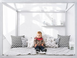 Serious little boy sitting on a bed with a set of pillows. - 239167090