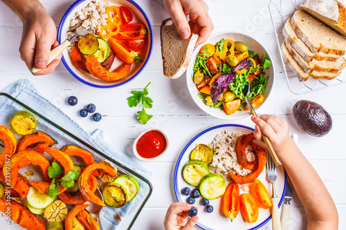 Family eating a healthy vegetarian food. Vegan lunch table top view, plant based diet. Baked vegetables, fresh salad, berries, bread on a white background. - 239171677
