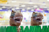 2 brown t-rex model toys head up from plastic grass in the kids shop, Bangkok department store, Thailand.