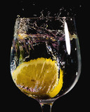 slice of lemon falling in to a glass of water