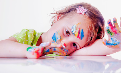 Art, creativity, beauty childhood concept. Portrait of little cute child girl with colorful hands and face.