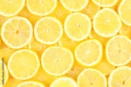 Leinwandbild Motiv A slices of fresh juicy yellow lemons.  Texture background, pattern.