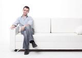 young man sitting on a modern sofa - 239223278