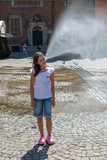A girl in front of a fountain in the Market Square of Wroclaw, Poland.