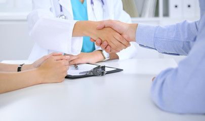 Doctor and patient shaking hands. Family couple at medical exam, just hands at the table. Medicine concept