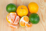Whole and slices of ripe green and orange tangerines