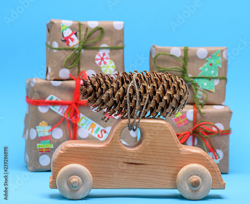 wooden machine carries a rope tied cone against a background of wrapped gifts
