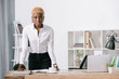 confident african american businesswoman with short hair standing near table in modern office